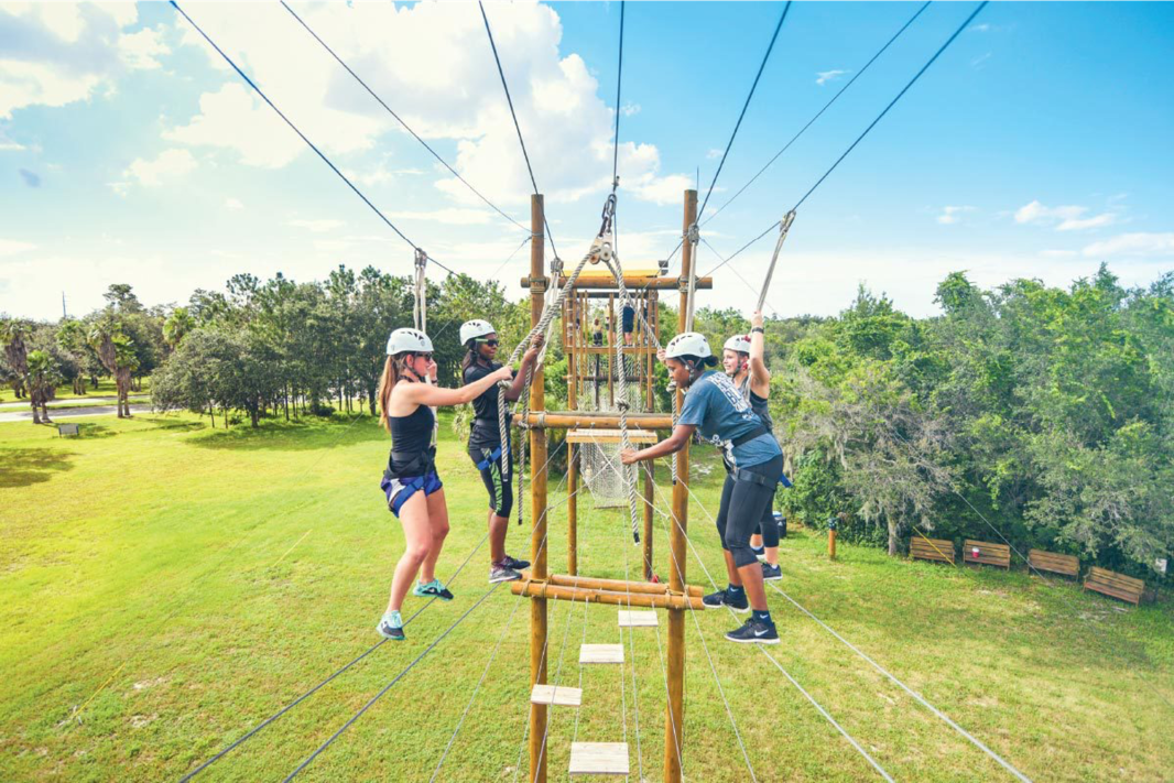 Students work together to get through a ropes course several feet in the air