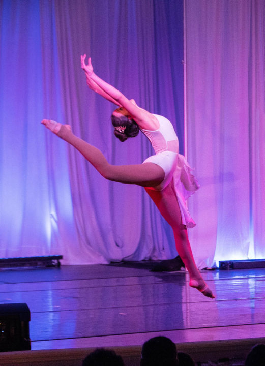 Young dancer performs and arabesque on stage