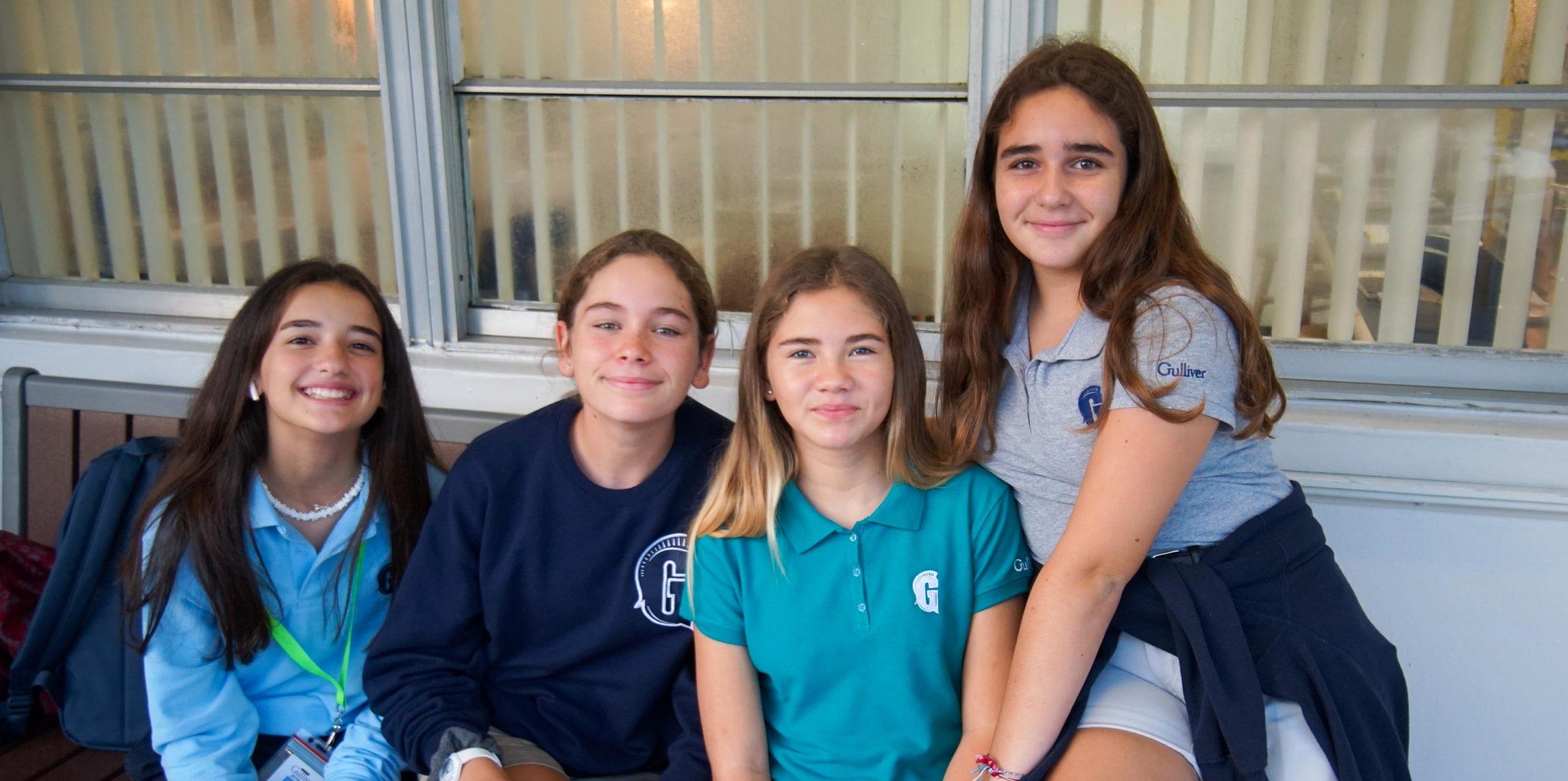 Four girls smiling outside
