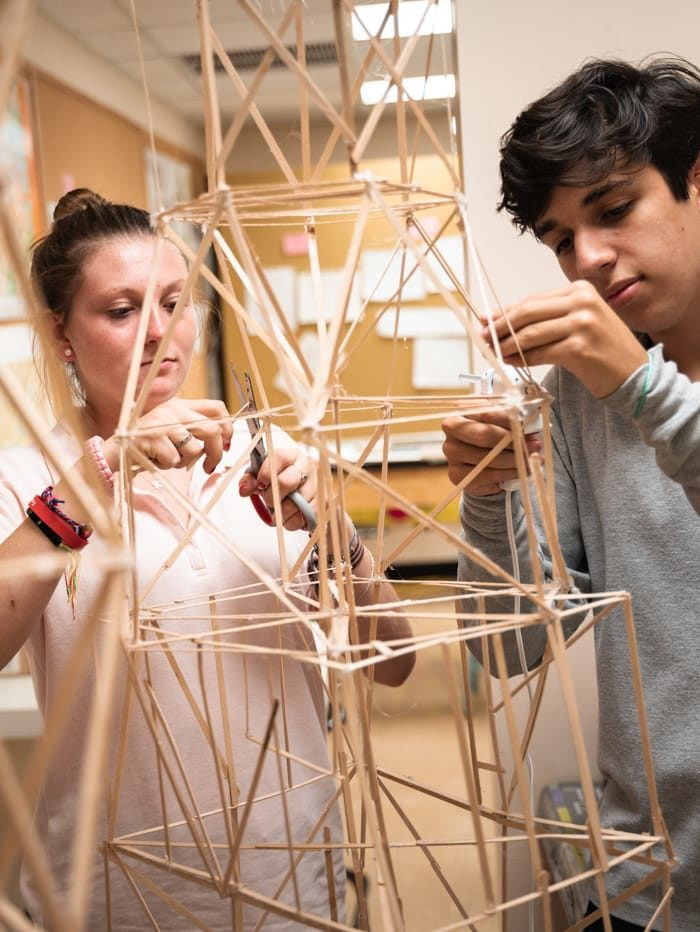 Two students building structures in architecture class