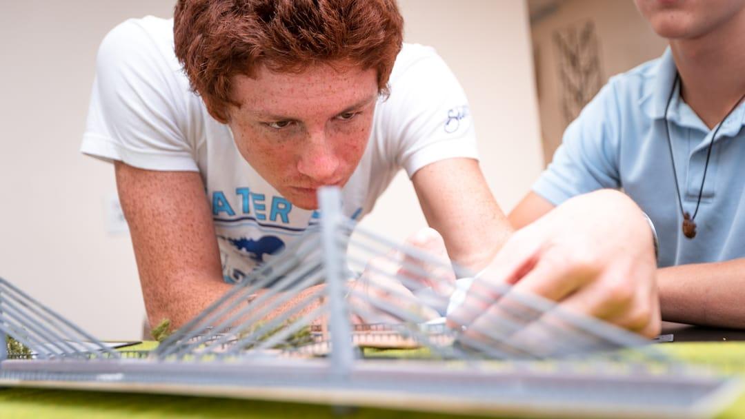 Male student building a bridge in architecture class