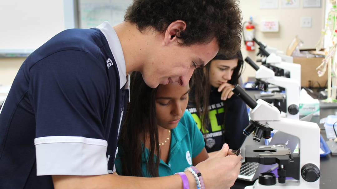 Two upper school students looking at a microscope in Biomedical science class