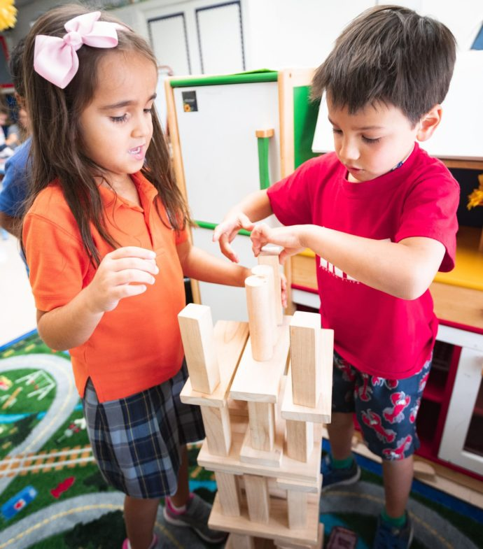 Two primary school kids building a structure with blocks