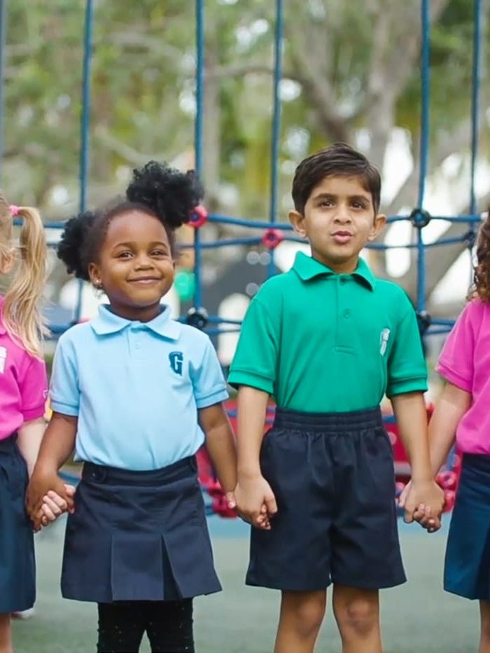 Four diverse children holding hands by the playground