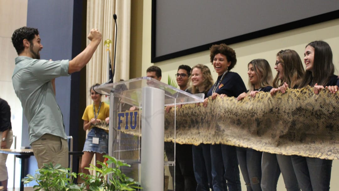 Upper school students in field studies holding a large snake skin