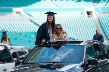 Grad and parent on car