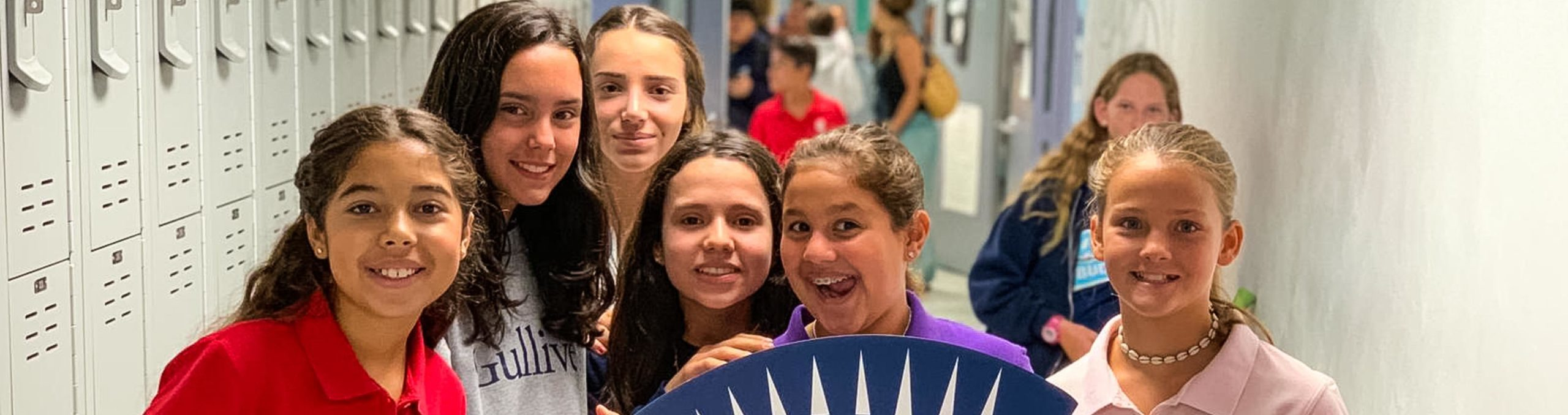 students holding a giant Gulliver foam logo