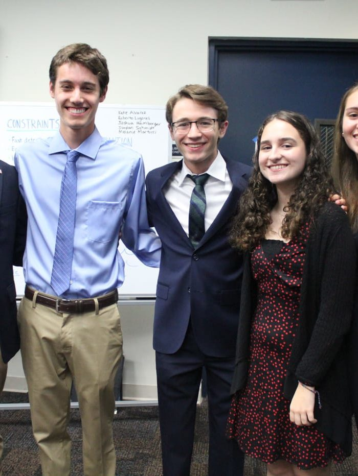Five International Diplomacy & Law students standing in formal attire