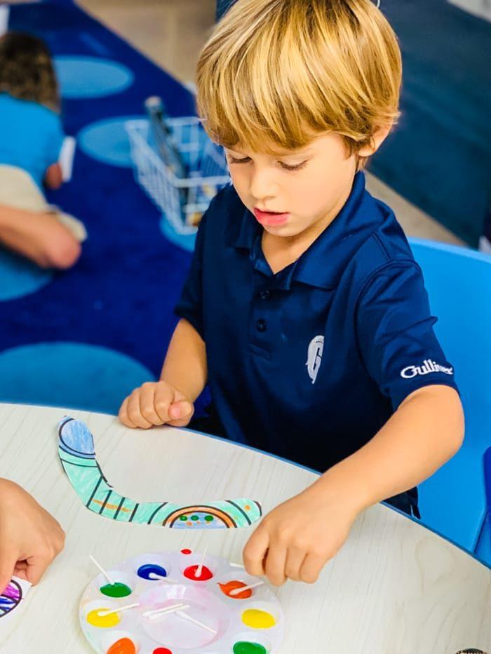 Boy coloring a paper boomerang