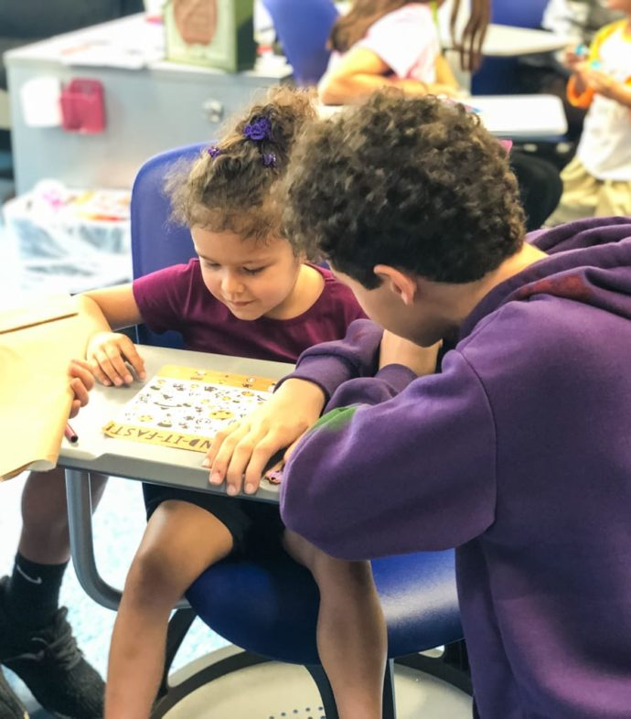 Staff helping young student learn