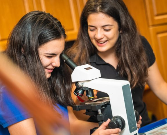 Two girls looking through a microscope