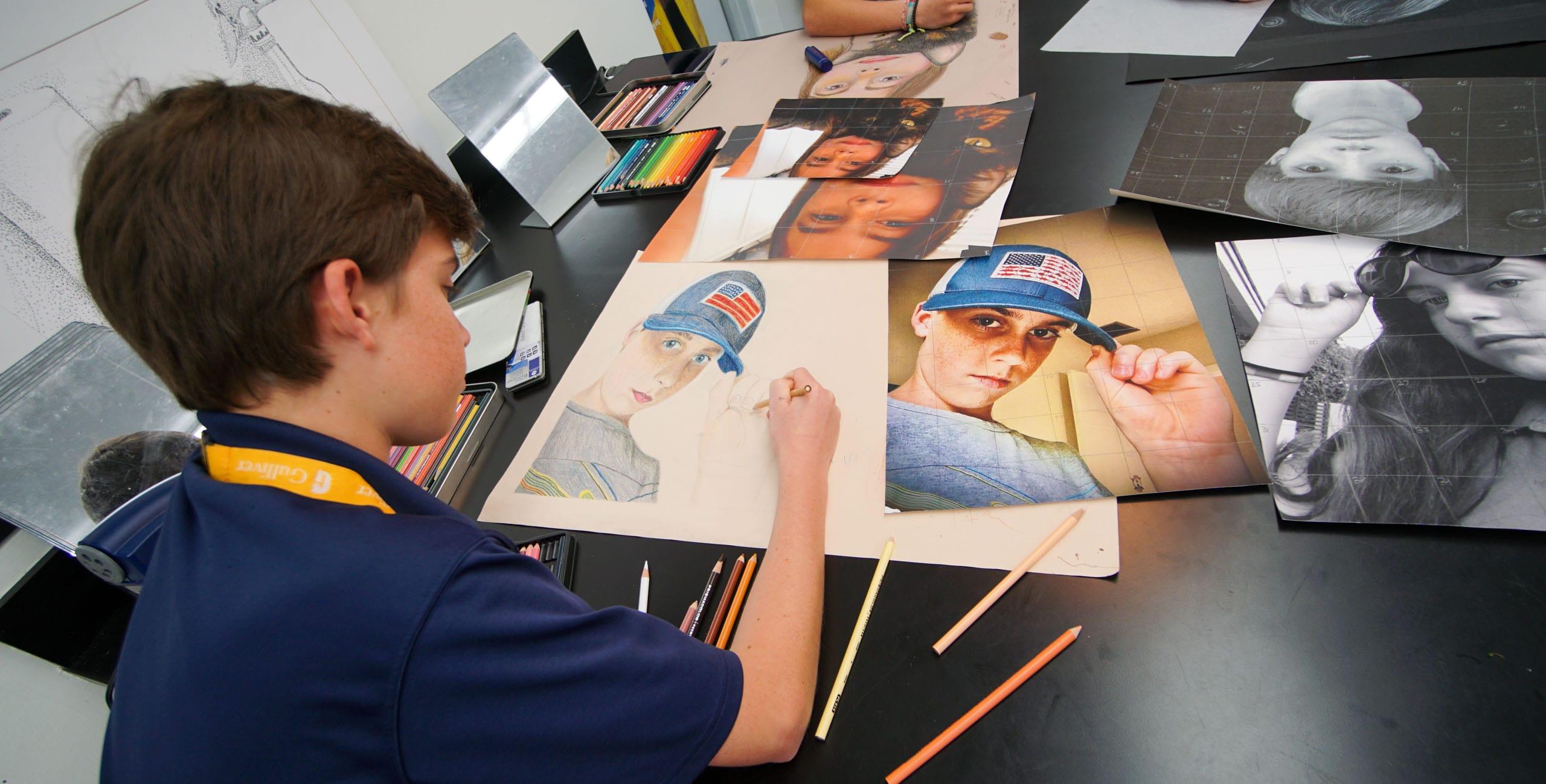 Male student coloring a self portrait
