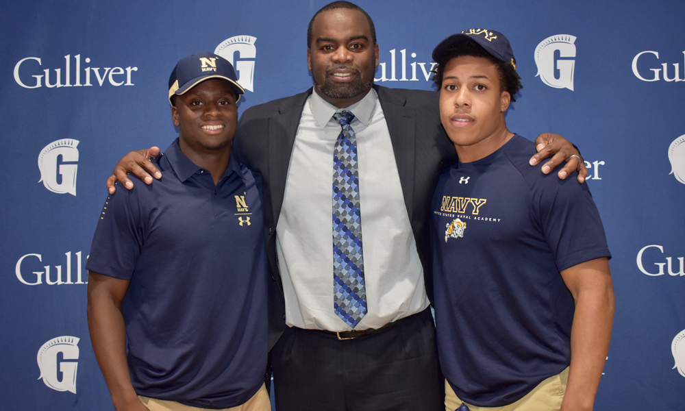 Two teenage boy football signees with coach