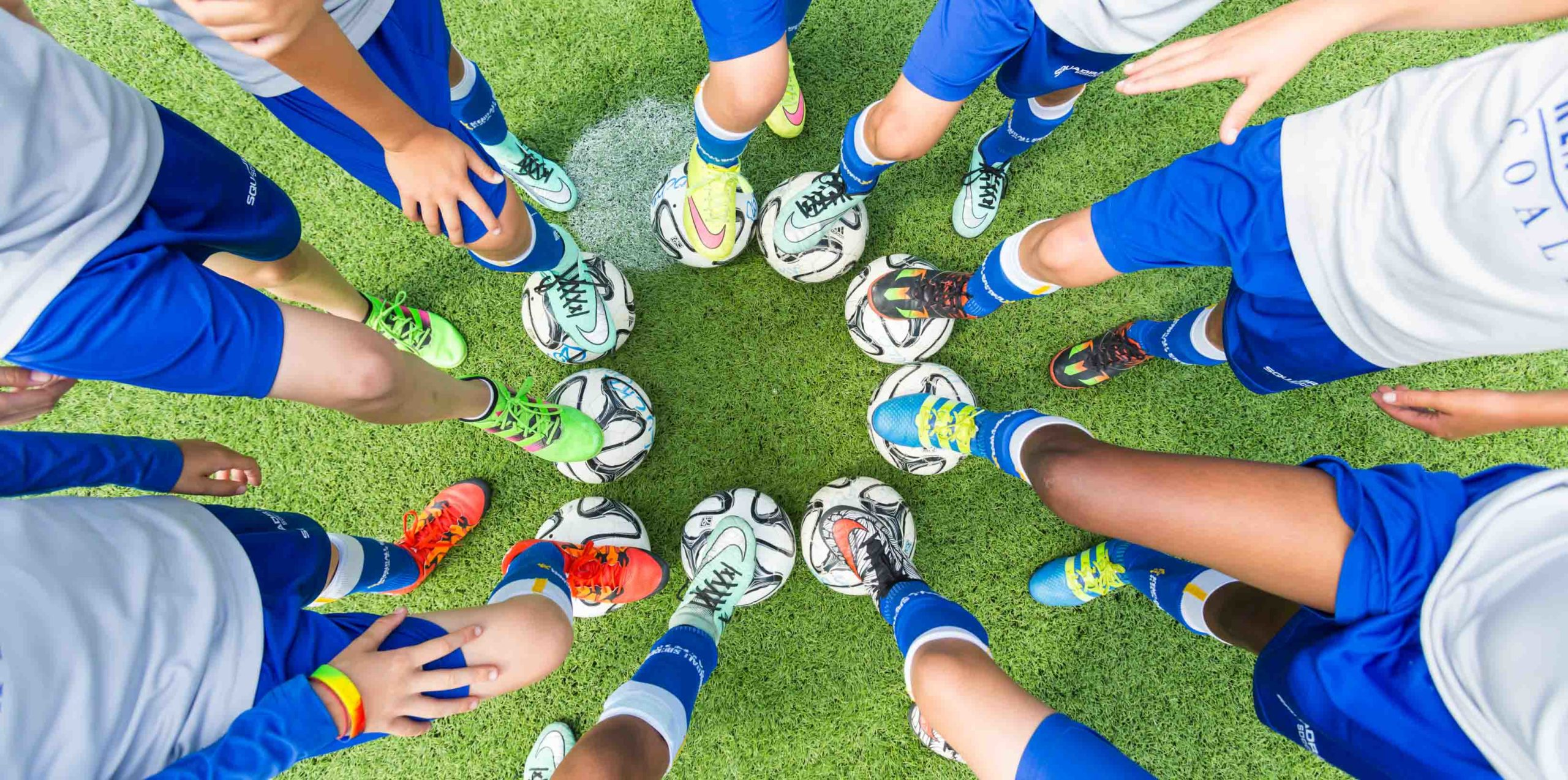 Students with feet on soccer balls
