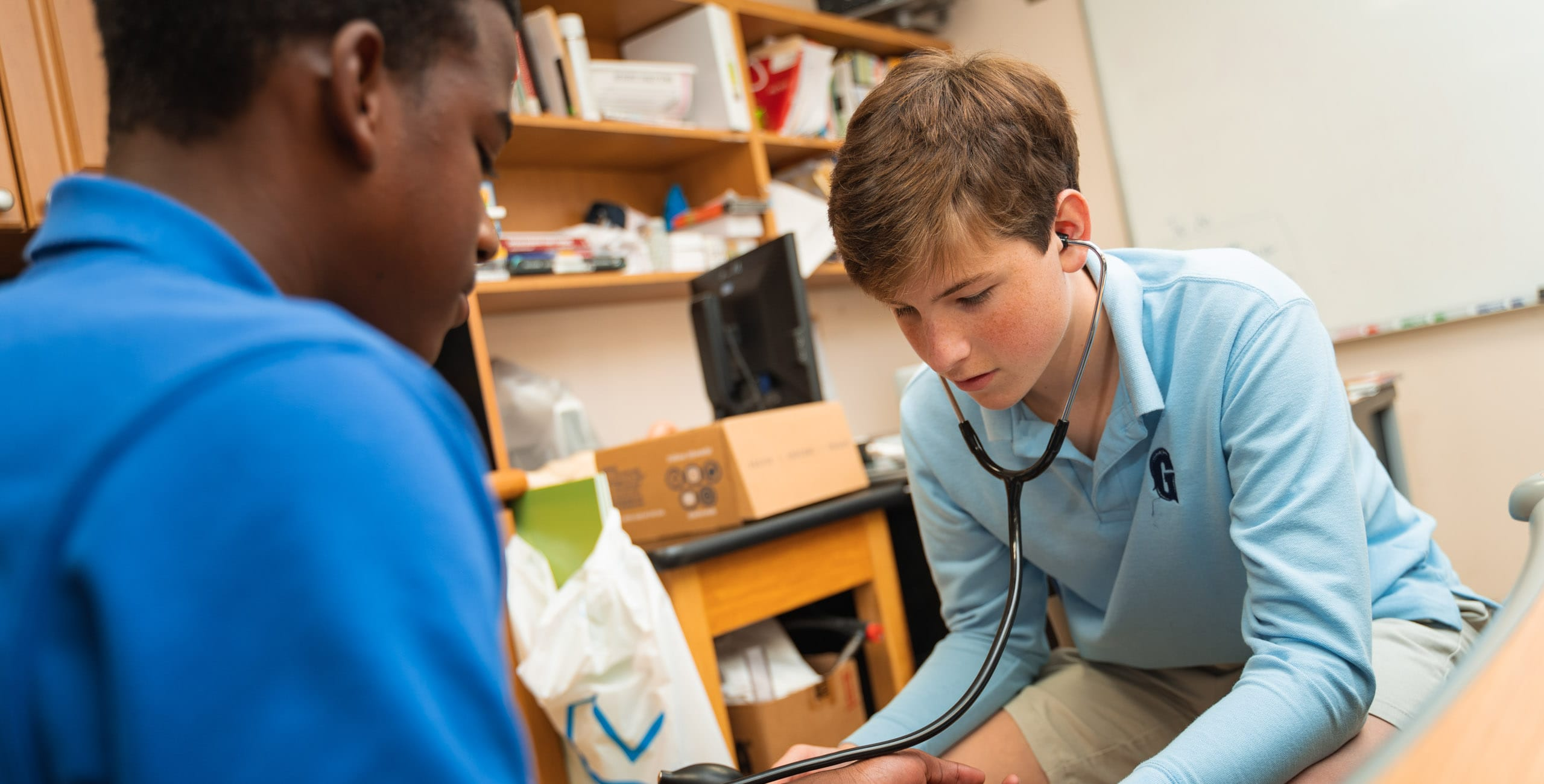 Student checking heartbeat of another student with a stethoscope