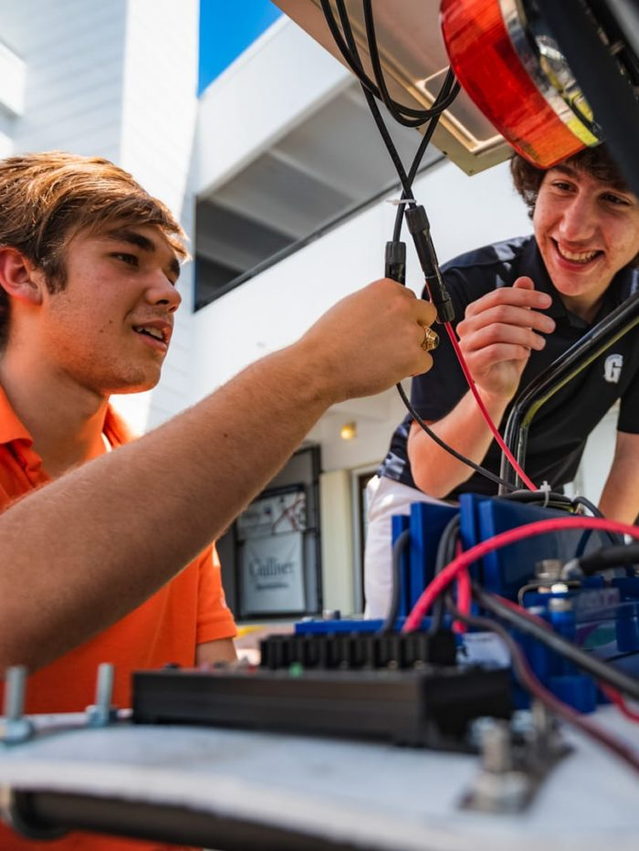Two students connecting wires for a solar vehicle project