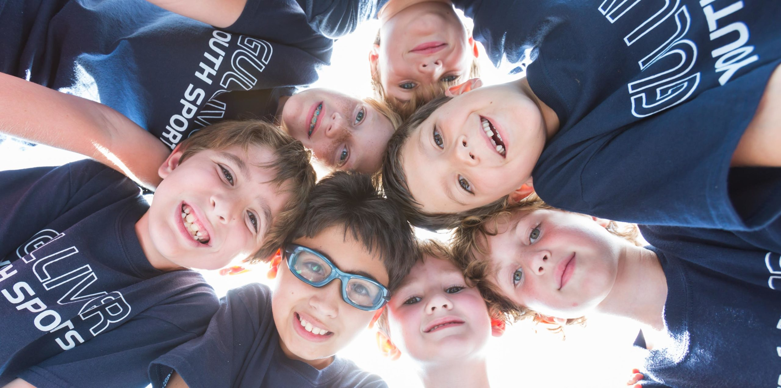Young students in a circle smiling and looking down