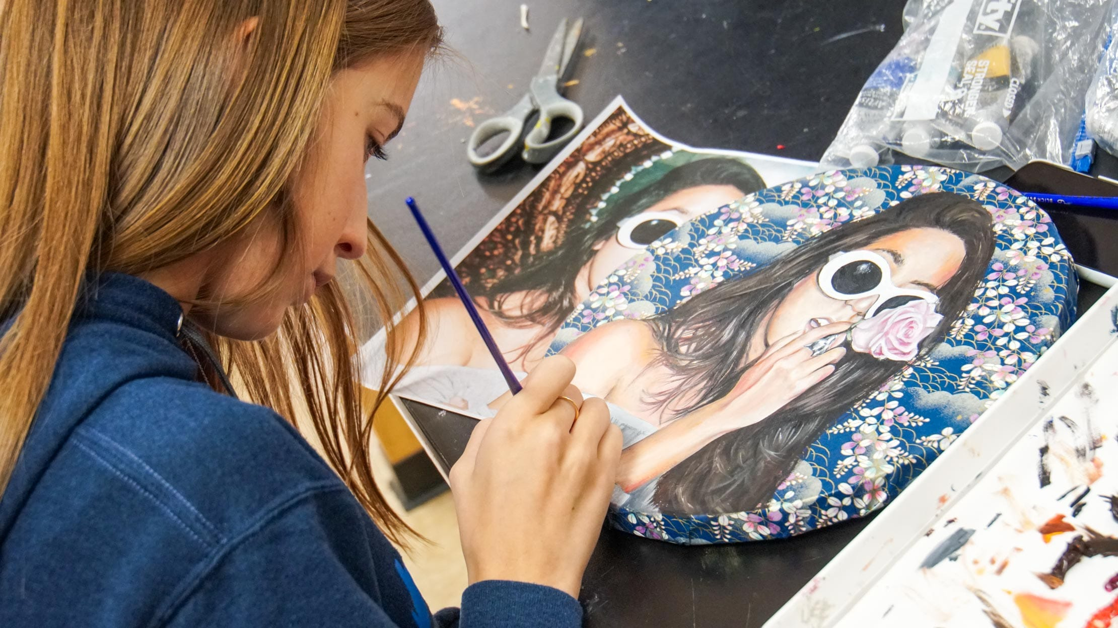 Student painting in visual arts class