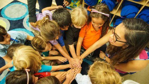 Lower school students circle with hands in