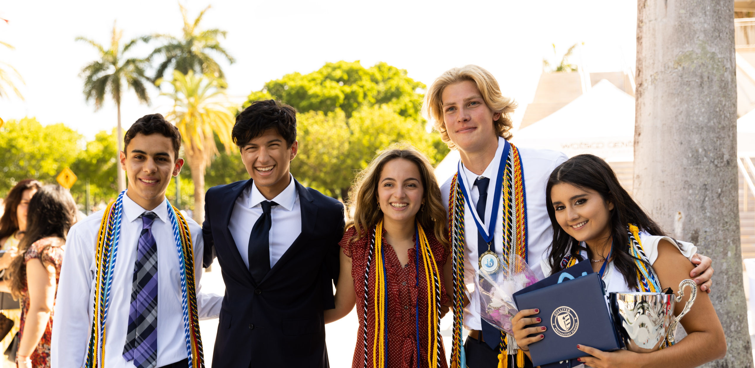 Five graduates smiling for a photo after commencement