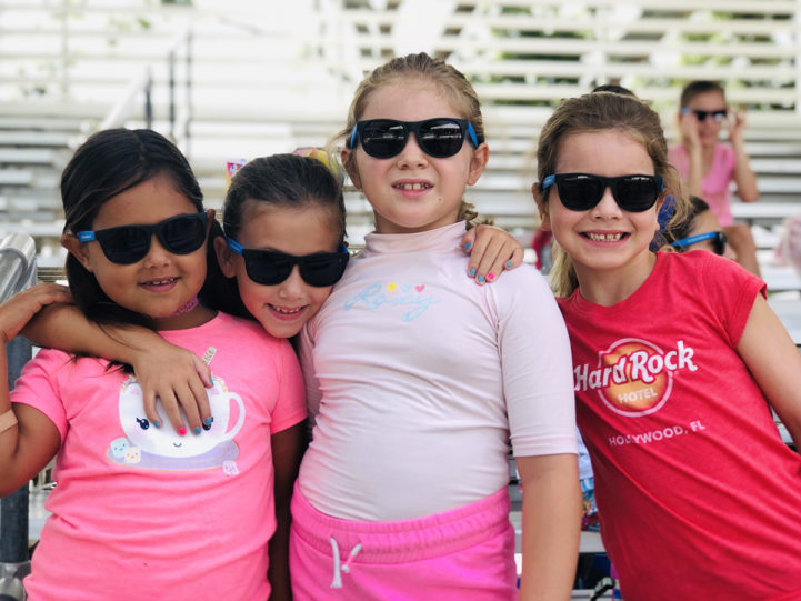 4 girls wearing sunglasses and smiling at camp