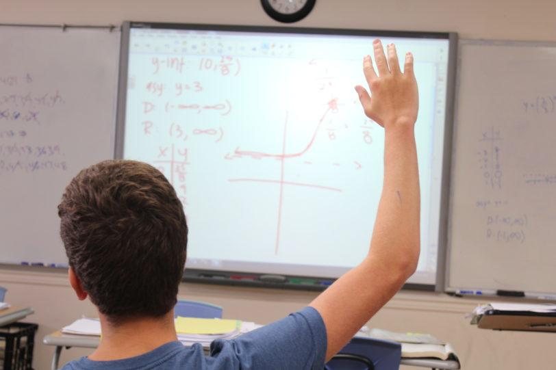 Student raising hand during class.