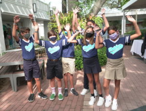 6 students cheering in the courtyard