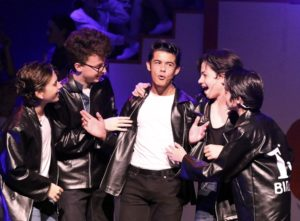 Actors performing during the production of Grease