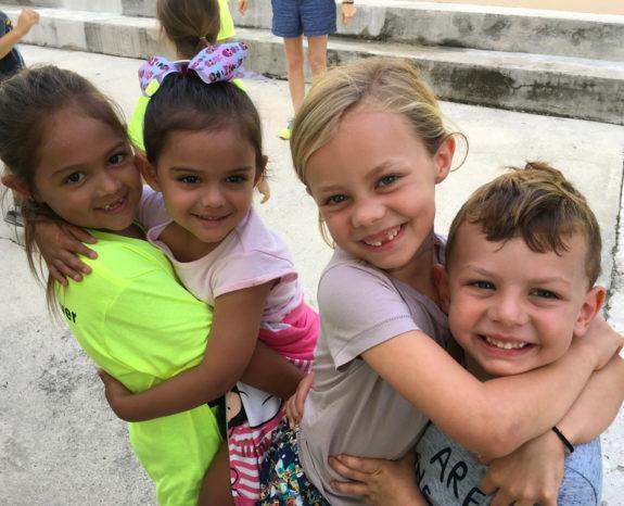 Kids hugging and smiling.
