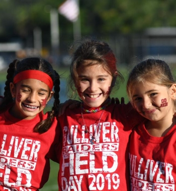 Three girls smiling and wearing raider's shirts
