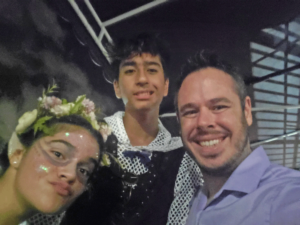 James Johnson is a Middle School English teacher, pictured here with students after a school theatre production.