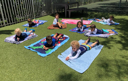 Kids laying on towels in the sun.