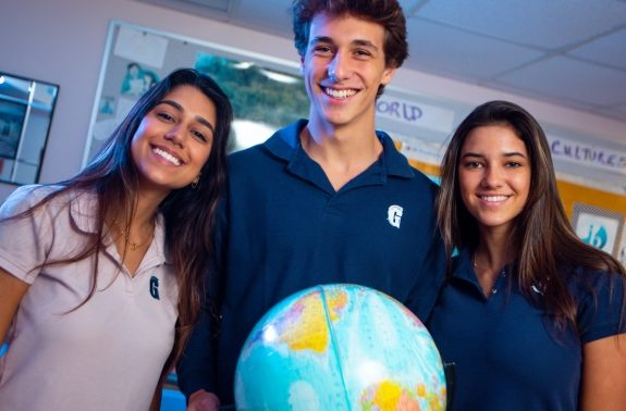 Three students stand behind globe