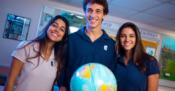 Three students stand behind globe