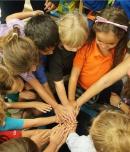 Students put hands in a circle